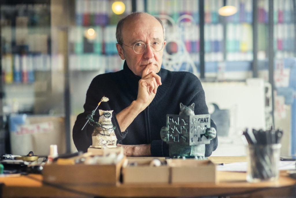 Photo représentant le dessinateur, sculpteur et humoriste Philippe Geluck travaillant à sa table à dessin.